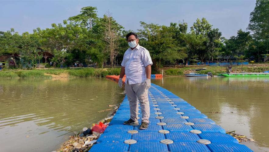 Ade Yunus, founder of environmental organisation Bank Sampah Sungai Cisadane (Cisadane River Waste Bank) or Banksasuci, stands on a floating boom used to collect waste from the Cisadane River in Tangerang, Indonesia. Image by Adi Renaldi. Indonesia, undated.