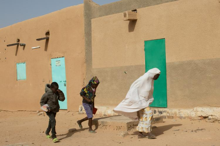 A woman and two children walk through strong winds in Agadez, Niger. Image by Joe Penney. Niger, 2018.