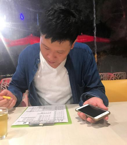 Wei Jiang orders dinner for an English-speaking journalist using his cell phone's Google Translate app to communicate with her. Image by Melissa McCart. Taiwan, 2018.