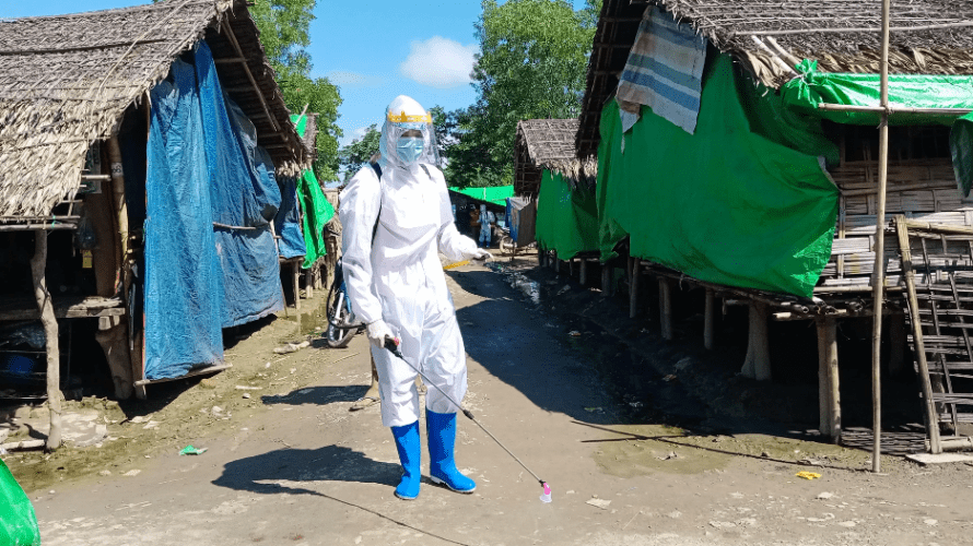 A volunteer sprays chemical disinfectant on shelters in Tain Nyo Internally Displaced Person Camp in Mrauk-U township, Rakhine State, Myanmar, as a COVID-19 prevention measure. Taken on September 2, 2020. Myanmar, 2020.