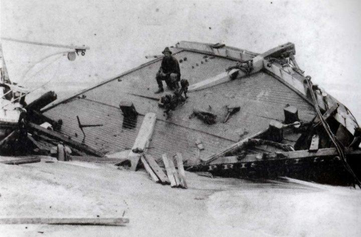 Rasmus Midgett sits on the wreckage of Priscilla in 1899. Image courtesy of NC Division of Archives and History. United States, 1899.