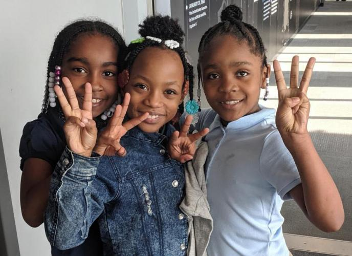 Students visiting the Peoria Riverfront Museum last fall hold up three fingers to show how many times they've visited the museum as part of the Every Student Initiative. Image by Peoria Riverfront Museum. United States, 2019.