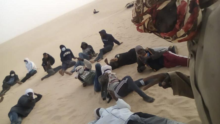This March 22, 2020 provided by migrant Tayeb Saleh shows fellow migrants resting in the sand while they await help getting out in the Libyan Sahara near the border with Sudan. (Tayeb Saleh via AP)