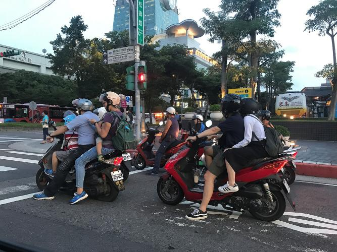 Taiwanese commuters often rely on scooters, sometimes crowding a whole family onto one of these vehicles. Image by Melissa McCart. Taiwan, 2018.