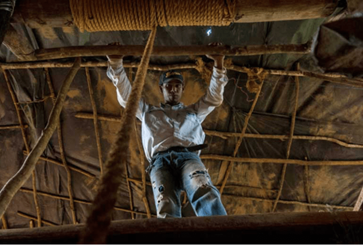 A small-scale miner awaits as the author is winched up after descending 40 meters (130 feet) into a Venezuelan mining shaft. Image by Bram Ebus. Venezuela, 2017.