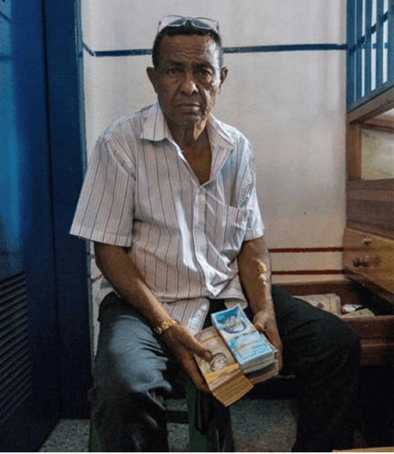 The owner of a local gold pawn shop in Tumeremo, Bolivar state, shows a stack of Venezuelan money, worth only a few dollars due to the nation's rapidly escalating inflation. Image by Bram Ebus. Venezuela, 2017.<br />
