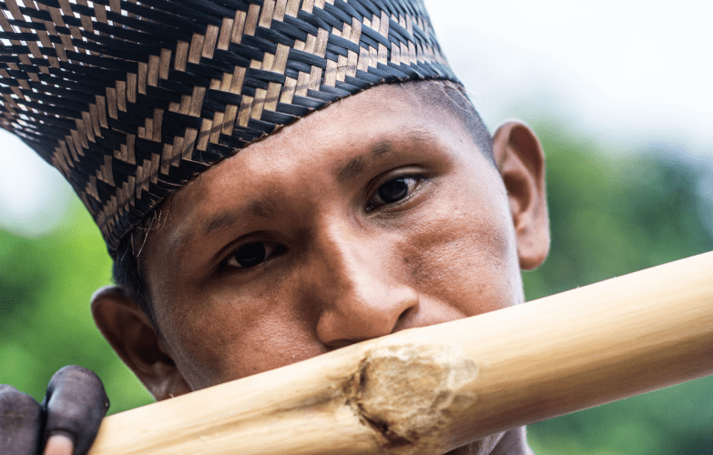 Playing on a bamboo flute during ritual preparations. Photo by Matheus Manfredini. Brazil, 2019.