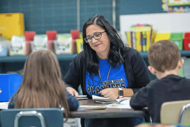 Niva Vargo works with her students on a reading activity. Image by Andrew Rush. United States, 2019.
