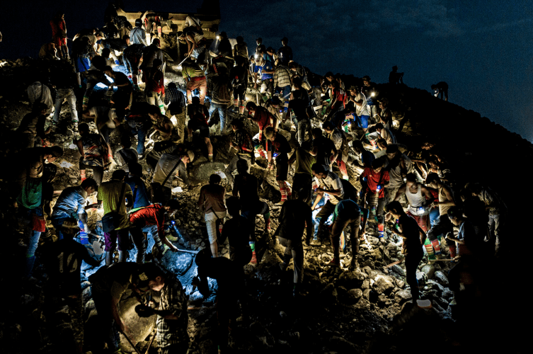 Freelance miners search for jade stones at night with torchlights on a waste site in Hpakant on May 18, 2019. Image by Hkun Lat. Myanmar, 2019.