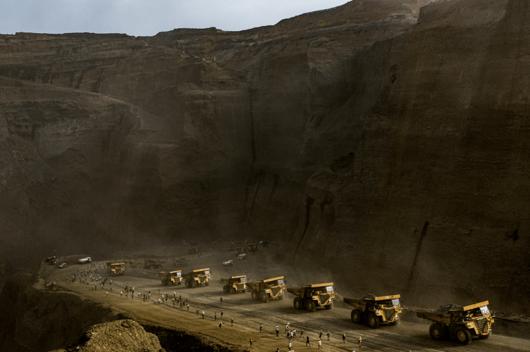 Freelance jade miners rush past a line of company trucks during a two-hour break at a government-licensed jade mining site, when they are allowed to search through discarded tailings but must turn over larger stones to the mining company, in Hpakant on May 17, 2019. Image by Hkun Lat. Myanmar, 2019.