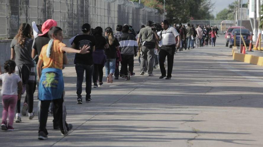A line of migrants is led toward the Mexican Instituto Nacional de Migracion where they will be processed once they're sent back to Mexico from the United States. Image by Jose A. Iglesias. Mexico, 2019.