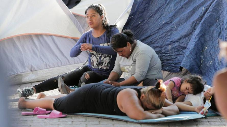 A migrant family waits in the shade on the Matamoros side of the Gateway International Bridge. Many migrants who cannot afford to rent rooms stay in this makeshift camp while waiting to ask for asylum in the United States. Image by Jose A. Iglesias. Mexico, 2019.
