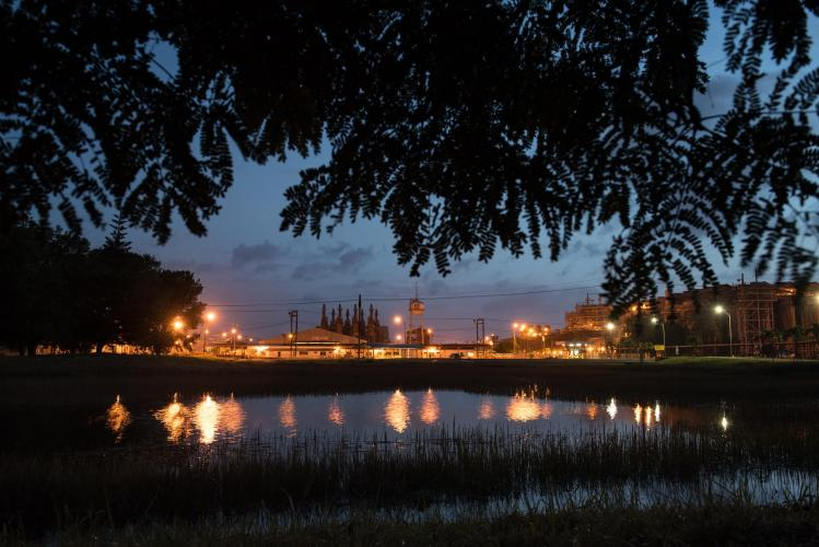 The sky at dusk is cut by the orange glow of the refinery at the Paranam Operations for Suralco, a subsidiary of Alcoa. The plant is no longer operational. Image by Stephanie Strasburg/Pittsburgh Post-Gazette. Suriname, 2017.