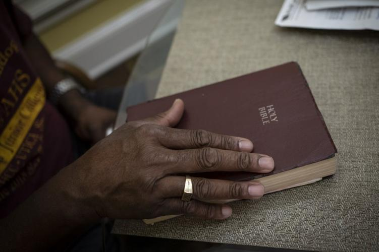 Mike Bishop closes his Bible after reading a passage from the Book of Psalms. Image by Wong Maye-E/AP Photo. United States, 2020.