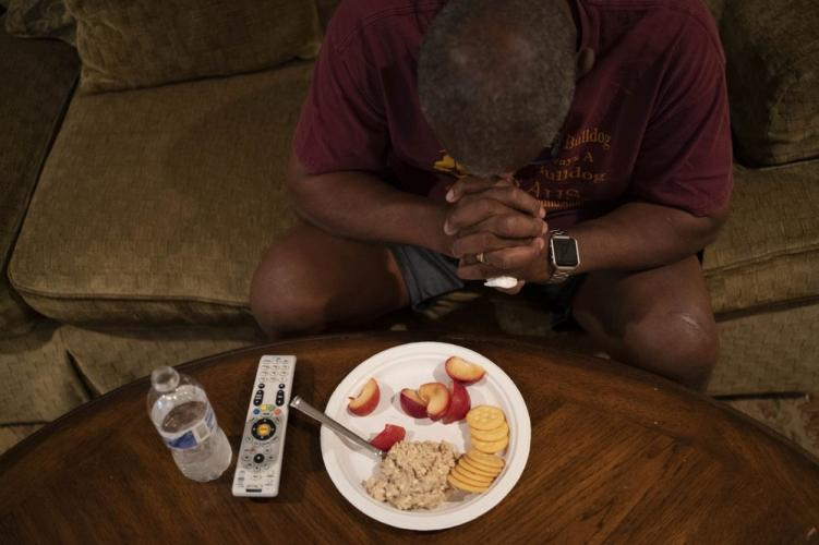 Mike Bishop prays before his dinner in front of the television in his living room. Image by Wong Maye-E/AP Photo. United States, 2020.