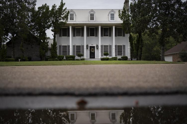 The house of Mike and Bonnie Bishop is reflected in a puddle. Image by Wong Maye-E/AP Photo. United States, 2020.