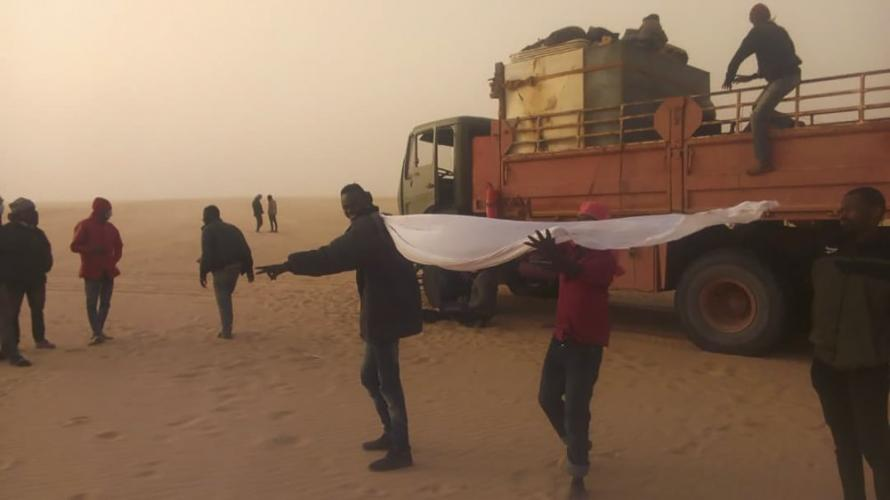 This March 22, 2020 provided by migrant Tayeb Saleh, shows fellow migrants standing in the sand while they await help getting out in the Libyan Sahara near the border with Sudan. (Tayeb Saleh via AP)