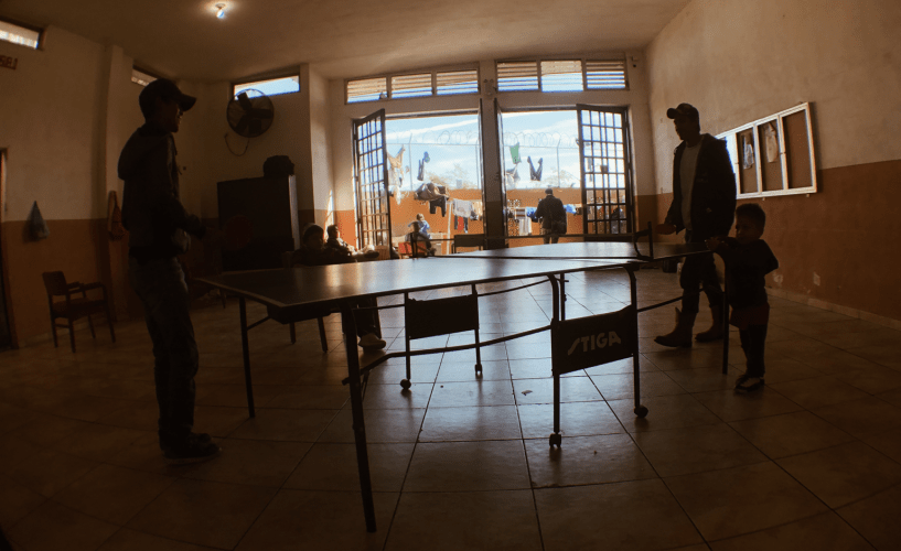 Migrants at a ping pong table before the Nazareth shelter closed to newcomers. Image by Daniel Mendez. Mexico, 2020.