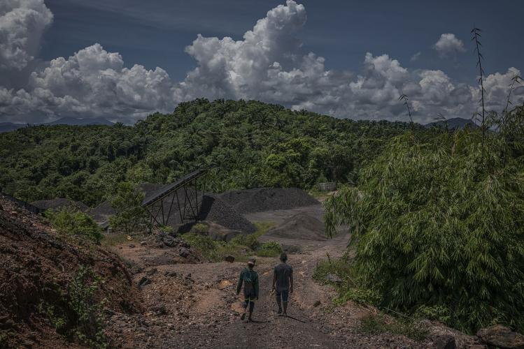 Hassan, left, and Li walk through the manganese mine processing area right above their Kuala Koh settlement. Image by James Whitlow Delano. Malaysia, 2019.