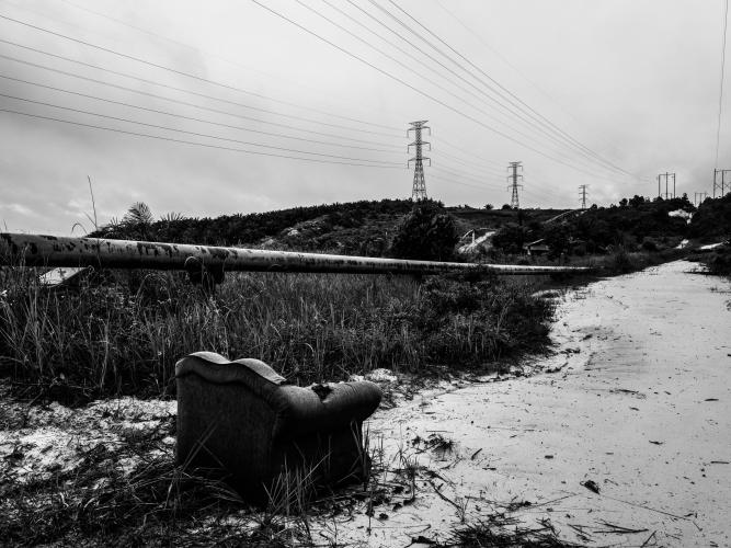 A pipeline carries fossil fuels—another kind of crude—alongside a road in Kandis. Image by Xyza Cruz Bacani. Indonesia, 2018.