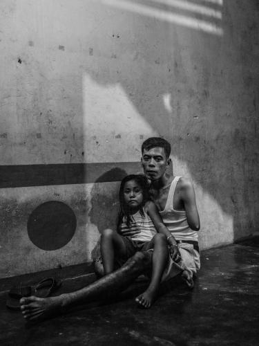 Misnan sits with his daughter Delisa in their home in Kandis. He lost his arm when he crashed his motorbike while carrying a scythe. He was on his way to work at a plantation. Image by Xyza Cruz Bacani. Indonesia, 2018.