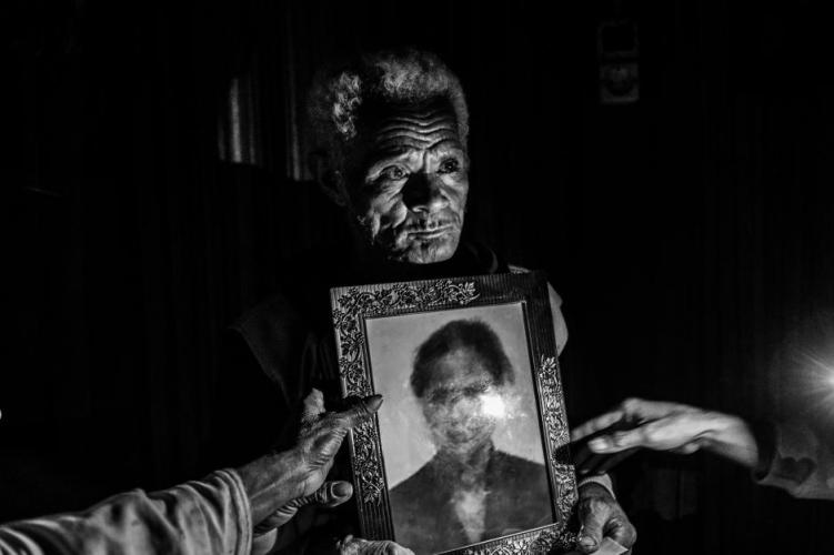 Martin Sauk shows a photo of his daughter Adelina Sauk, who was trafficked and later died in Malaysia. Image by Xyza Bacani. Indonesia, 2018.