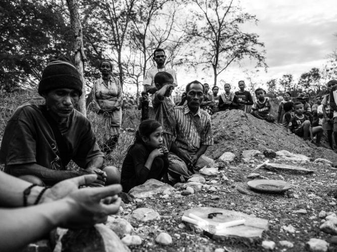 Mikhael and his grandchildren, together with other villagers, pray at a makeshift grave for Dolfina. Image by Xyza Bacani. Indonesia, 2018.
