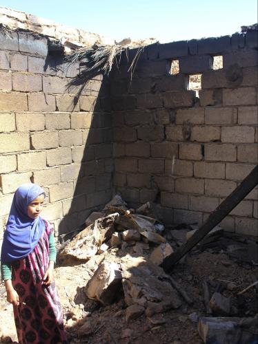 A girl stands in the burnt-out remains of a house destroyed during the U.S. Navy SEAL raid in the village of al Ghayil on January 29. Image by Iona Craig. Yemen, 2017.