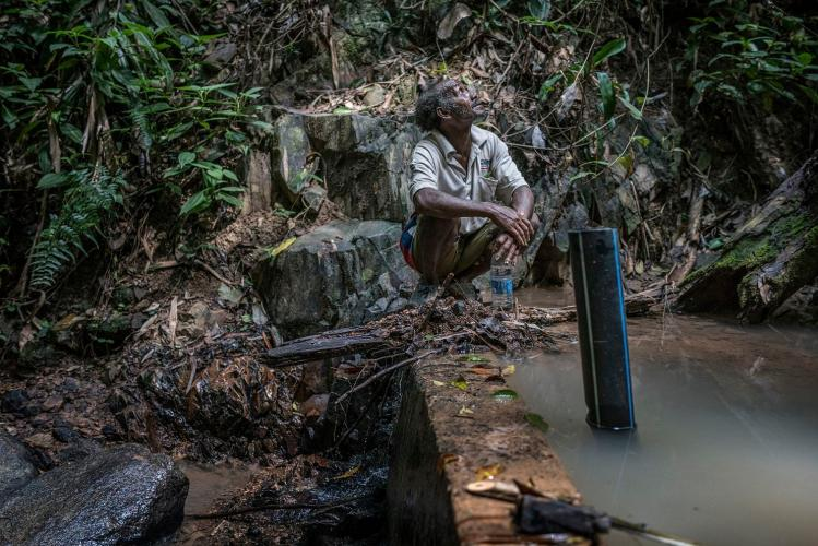 Johan Tahun takes a break atop the small concrete dam across the Tonduk River, built by the Malaysian government. Image by James Whitlow Delano. Malaysia, 2019.