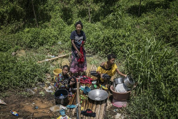 A mother and her two daughters wash pots and clothing at the water source that most Batek believe was contaminated by mining runoff. Despite that, they still use it as their primary water source. Image by James Whitlow Delano. Malaysia, 2019.