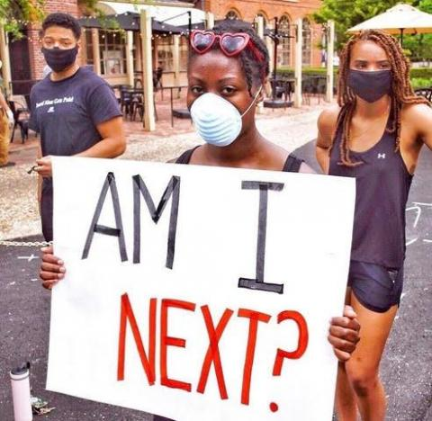 "Hayes, wearing a medical face mask, holds up a sign that reads ""Am I next?"" Two other young people stand in the background."