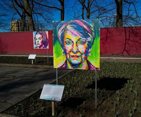A colorful portrait in an outdoor exhibit. There is another portrait in the background.
