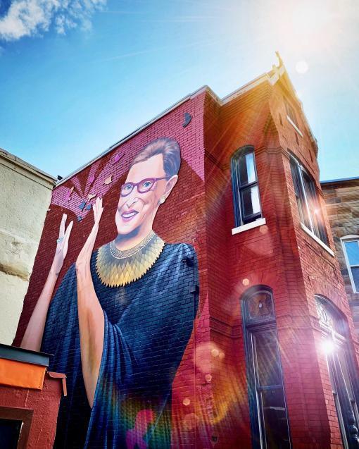 A mural of Ruth Bader Ginsburg on the side of a red brick building.