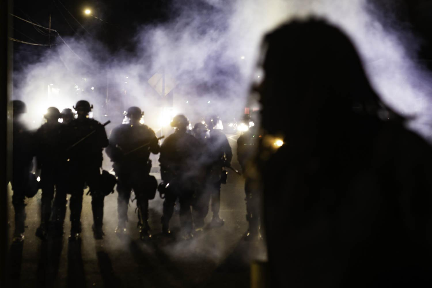 A protester crosses the street as a line of Portland police officers approach amidst a cloud of teargas on the night of August 9, 2020.