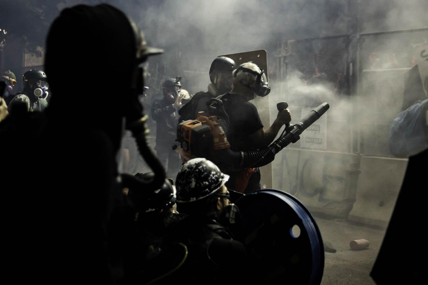 A man in a gas mask and with a leafblower stands next to a police barricade as tear gas fills the air