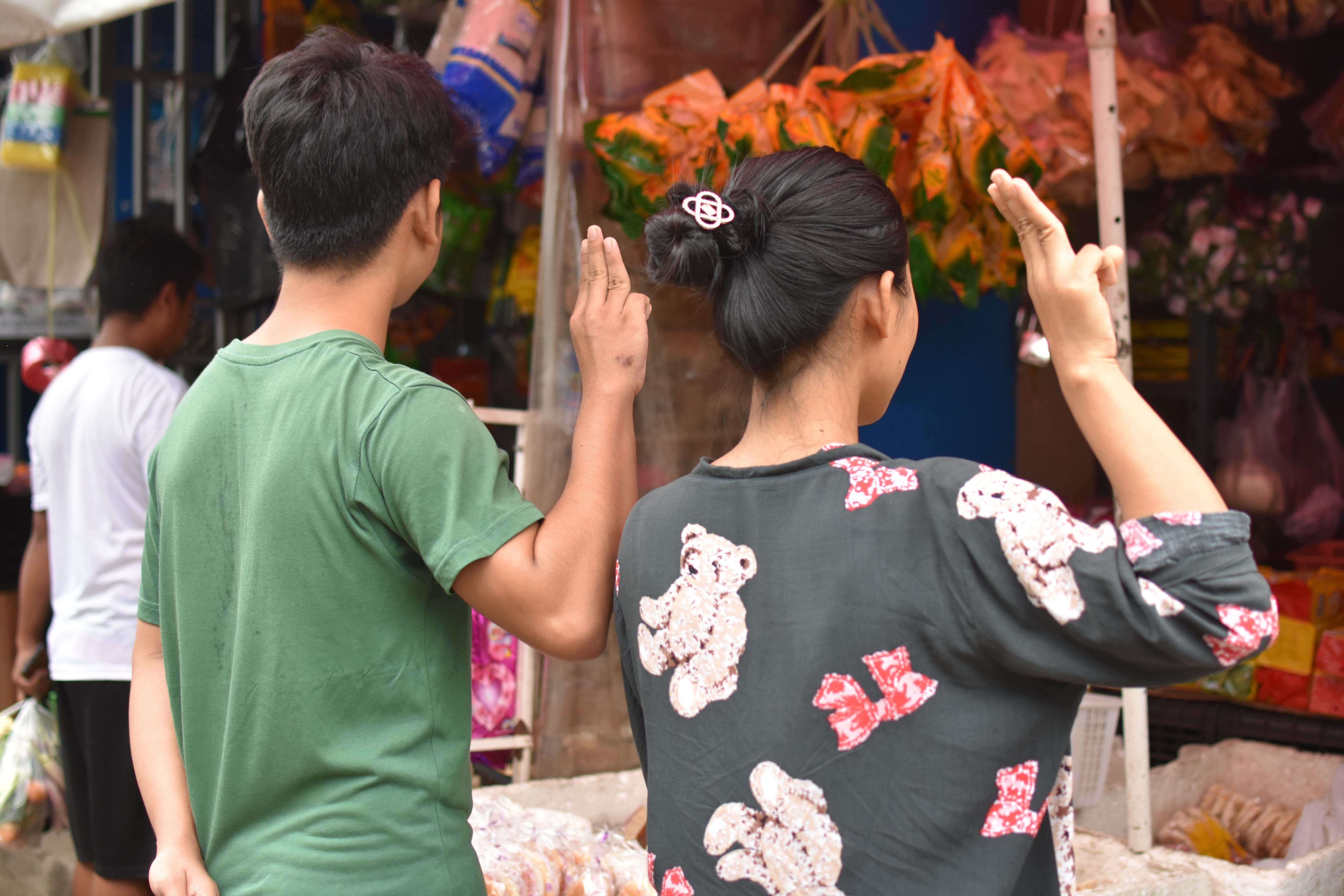 A man and woman hold up three fingers with their right hands in a market.