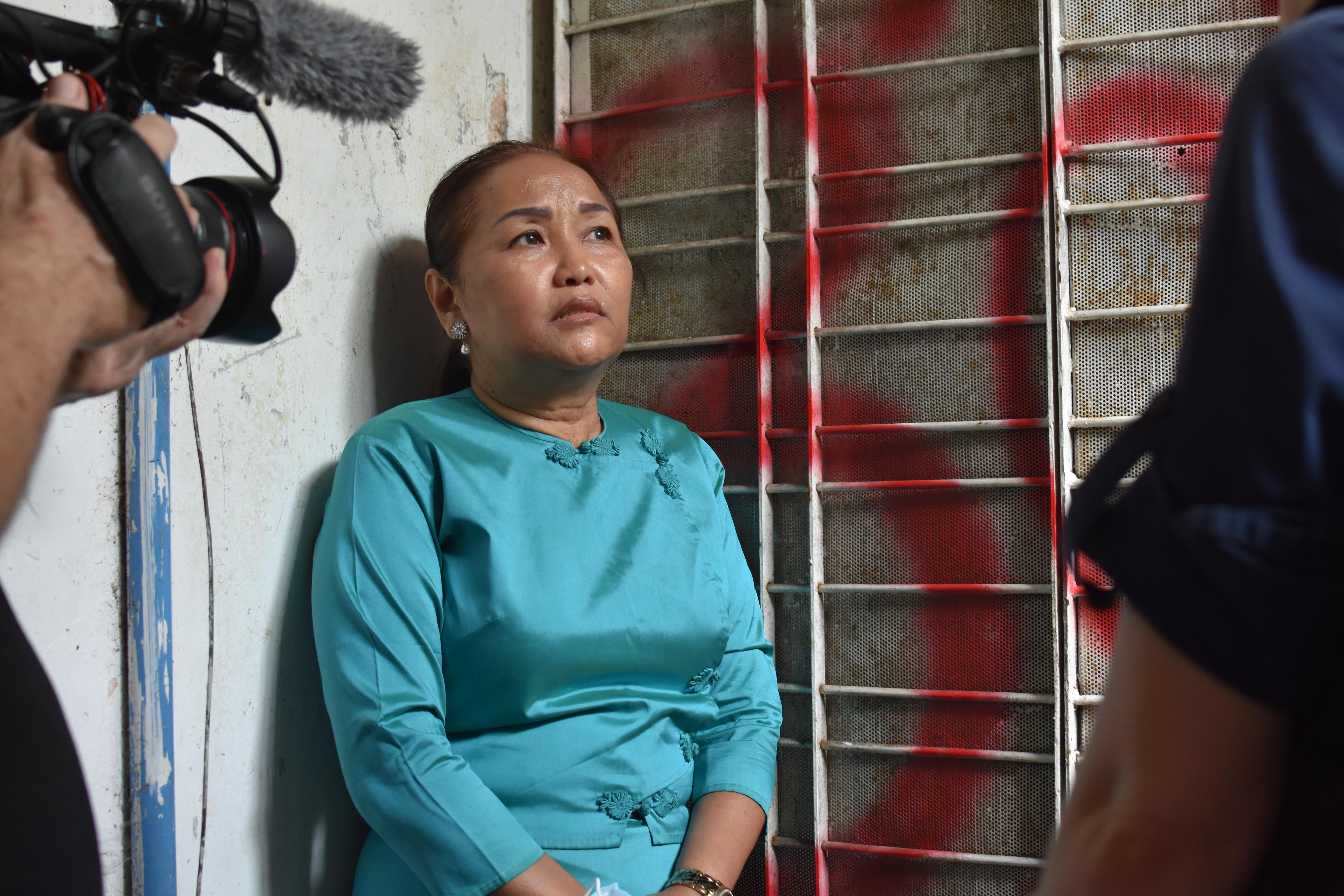 Le Le Naing Kyaw standing in front of her door, which was vandalized with red paint.