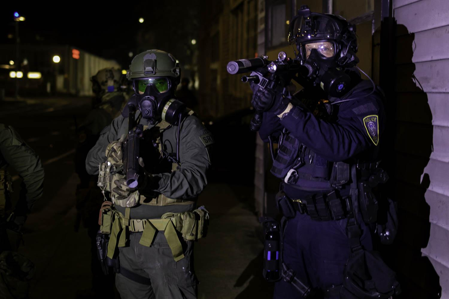 "Federal Department of Homeland Security officers point ""less-lethal"" munitions weapons at a group of protesters demonstrating near the Immigration and Customs Enforcement building on the night of January 20, 2021."
