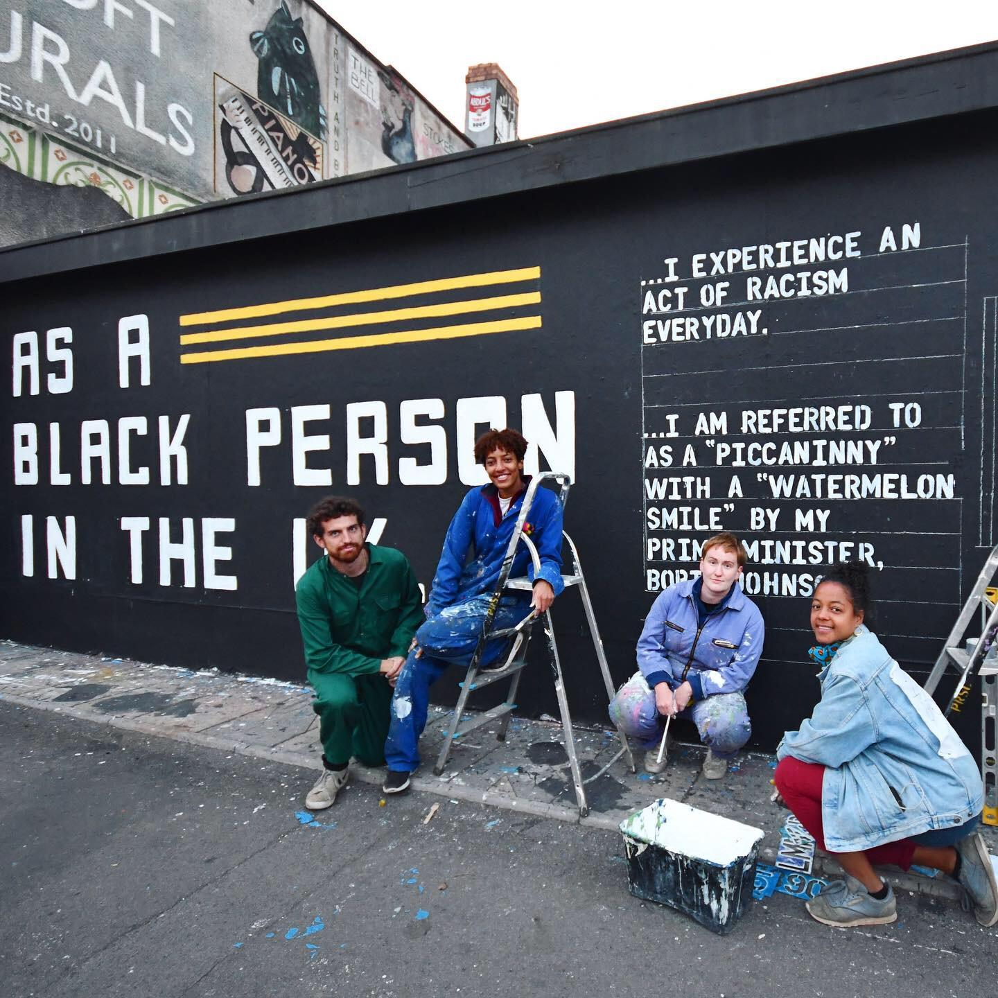 "Four people sit in front of a mural that reads, ""As a Black person in the U.K."""