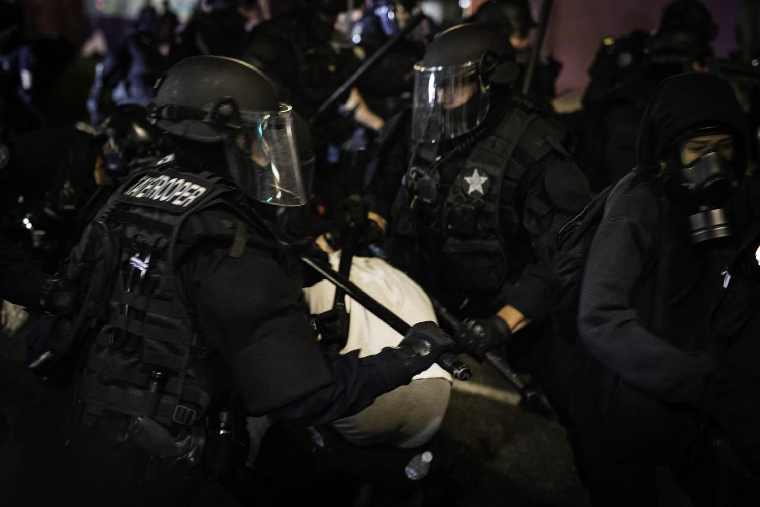 Oregon State Troopers use their clubs on a group of protesters in Portland, Oregon.