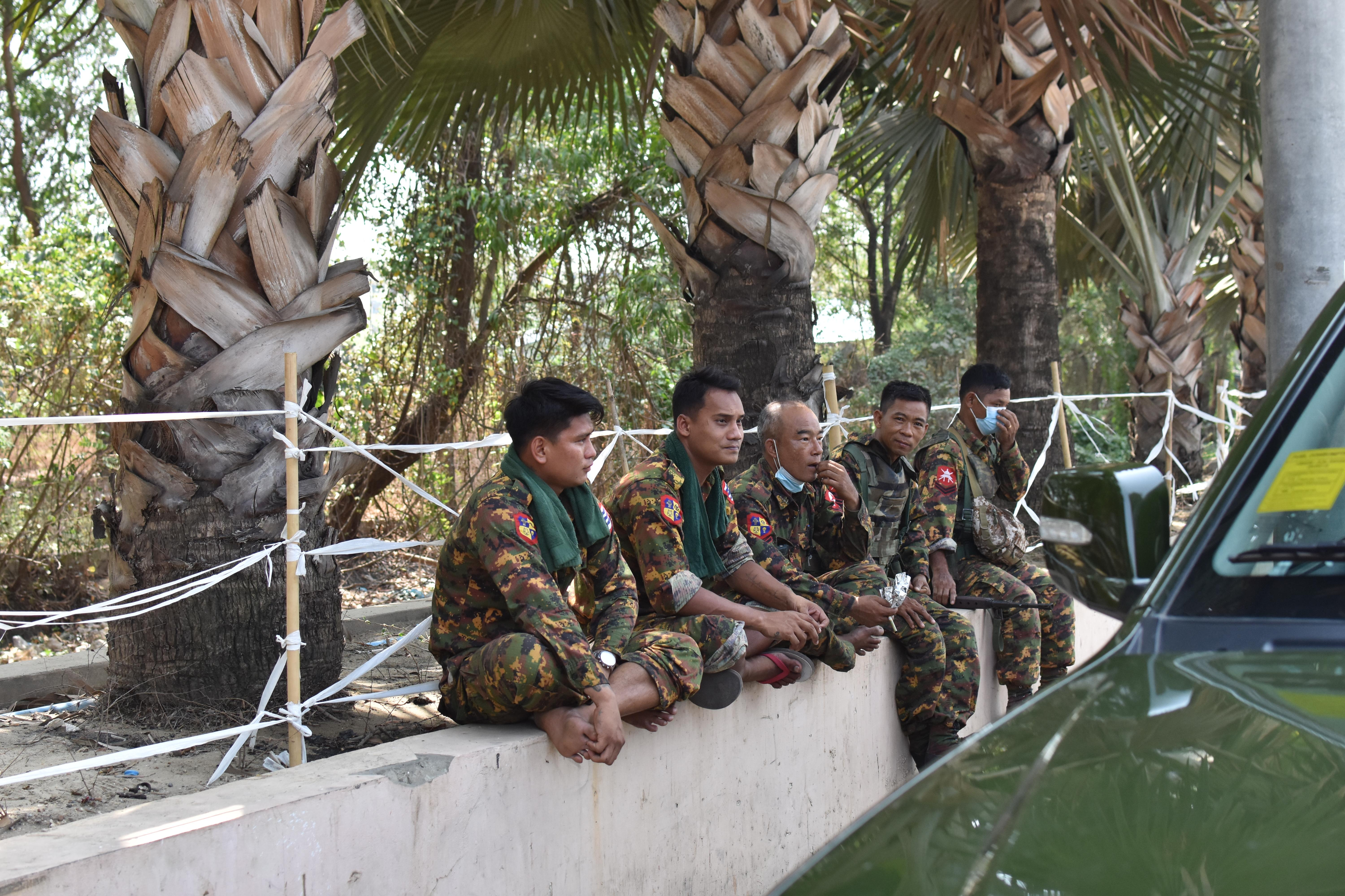 Soldiers sit on a wall in front of palm trees.