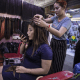 A hairdresser works on a customer at the Orussey shopping complex in Phnom Penh. Image by Paula Bronstein. Cambodia, 2019.